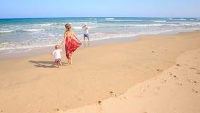 红色小女孩的母亲加入泡沫似的海浪负责的手 股票视频