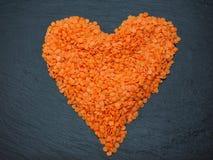 红色小扁豆在灰色板岩的心脏形状 免版税库存照片