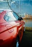 红色小轿车汽车在有欧洲议会的河前面停放了 免版税图库摄影