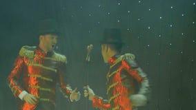 红色尾巴外套的两个时髦的人是跳舞和唱歌在阶段在剧院 股票录像