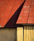 红色屋顶的阴影在老房子墙壁的 免版税图库摄影