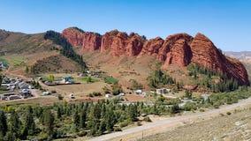 红色岩石在与绿色树和房子的天空蔚蓝下 库存照片