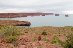 红色岩石在蓝色湖水中 免版税库存图片