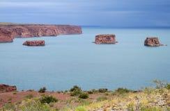 红色岩石在蓝色湖水中 库存图片