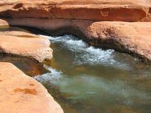 红色岩石打旋的水 免版税库存照片