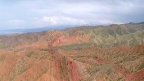 红色岩石空中录影与缺乏植被和遥远的积雪的峰顶的 影视素材