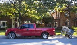 红色工作在传统邻里拾起有在街道上停放的水泥搅拌车的卡车 库存照片