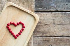 红色巧克力糖在木板材的心脏形状安排在木桌上的黄麻袋布料 免版税库存图片