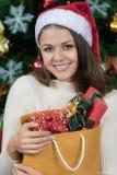 红色帽子和举行袋子的o年轻和美丽的白种人妇女 免版税库存照片