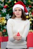 红色帽子和举行candl的年轻和美丽的白种人妇女 免版税库存照片