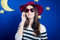 红色帽子和太阳镜的谈话微笑的女孩  免版税库存照片
