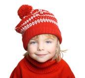 红色帽子和毛线衣的愉快的小男孩 免版税图库摄影