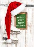 红色帽子和白色滑冰 快活的霍莉快活的圣诞节 免版税库存图片
