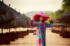 红色帽子的亭亭玉立的女孩在defocused伞中看下来 免版税图库摄影
