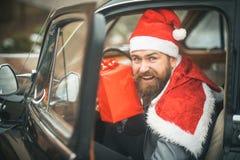 红色帽子的人交付在减速火箭的汽车的xmas礼物 免版税库存图片
