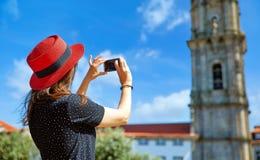 红色帽子的女孩拍照片 免版税库存图片