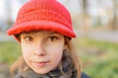 红色帽子的小美丽的微笑的女孩 免版税图库摄影