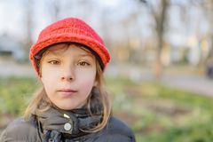 红色帽子的小美丽的微笑的女孩 库存照片
