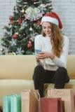 红色帽子的年轻美丽的白种人妇女坐沙发在fr 库存图片