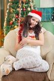 戴红色帽子的微笑的愉快的女孩拿着圣诞节礼物盒 库存照片