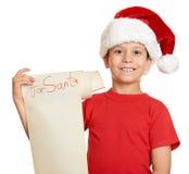 红色帽子的男孩有与愿望的长的纸卷信件的对圣诞老人 免版税库存图片