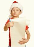 红色帽子的男孩有长的纸卷的祝愿对圣诞老人-寒假圣诞节概念,染黄定调子 库存图片