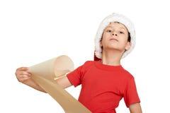 红色帽子的男孩有长的纸卷的祝愿对圣诞老人-寒假圣诞节概念 图库摄影