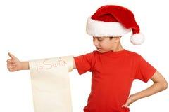 红色帽子的男孩有长的纸卷的祝愿对圣诞老人-寒假圣诞节概念 免版税图库摄影