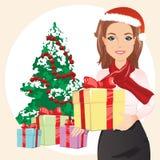 红色帽子的逗人喜爱的妇女在手上的拿着一件礼物在圣诞树和礼物的背景 库存图片