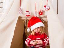 红色帽子的逗人喜爱的小女孩有玩具球的在手上临近圆锥形小屋 免版税库存图片