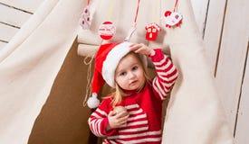 红色帽子的逗人喜爱的小女孩有玩具球的在手上临近圆锥形小屋 免版税库存照片