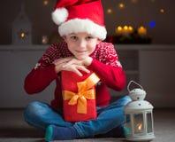 红色帽子的逗人喜爱的小男孩有礼物和latern等待的圣诞老人的C 免版税库存照片