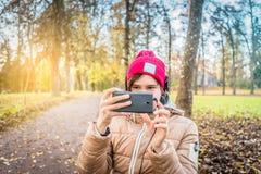 红色帽子的青少年的女孩,她的智能手机的射击的秋天公园 库存图片