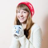 红色帽子&杯子:俏丽的有样式雪花的女孩和盖帽,有白色的毛线衣画象被编织的手套的热的饮料 免版税图库摄影