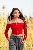 红色庄稼顶面毛线衣的一个美丽的女性白种人高三学生女孩 库存照片