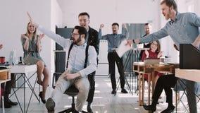 红色庆祝与公司队的EPIC-W愉快的乐趣年轻商人成功,乘坐的办公室椅子慢动作 股票录像