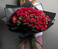 红色庭院玫瑰和芽大豪华的花束在黑包装纸,时髦 库存图片