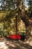 红色庭院长凳 免版税库存照片