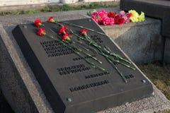 红色康乃馨在与下落的战士的名字的一块墓碑说谎胜利纪念品的 免版税库存照片