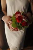 红色康乃馨花束在女孩的手上开花 免版税库存图片
