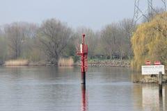 红色引导的岗位在河Hollandsche标记安全水路的IJssel在水中 免版税库存图片