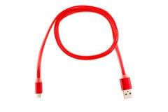 红色微型usb缆绳扭转了入一个圆环,在白色被隔绝的背景 水平的框架 免版税图库摄影