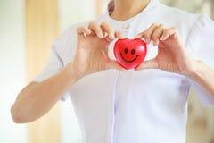 红色微笑的心脏由女性护士` s握两只手,代表给努力优质服务头脑患者 行业 免版税库存图片