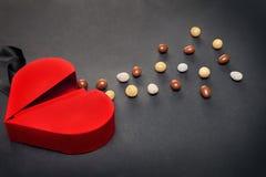 红色心形的箱子用巧克力糖衣杏仁为情人节 库存照片