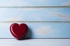 红色心脏倾斜的天蓝色木板 华伦泰概念 库存图片