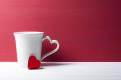 红色心脏倾斜的白色杯子 华伦泰概念 免版税库存图片