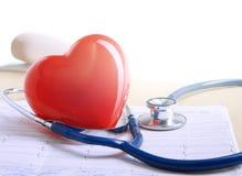红色心脏和一个听诊器在书桌上 免版税库存图片
