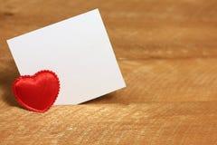 红色心脏和一张白色纸片 背景木头 图库摄影