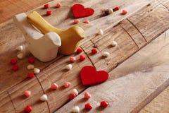 红色心脏和两只爱恋的鸟在木桌上 库存照片