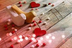 红色心脏和两只爱恋的鸟在木桌上 库存图片